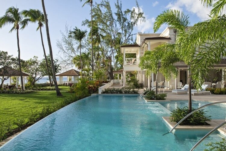 A large family villa in Barbados with a pool and palm trees in the front garden