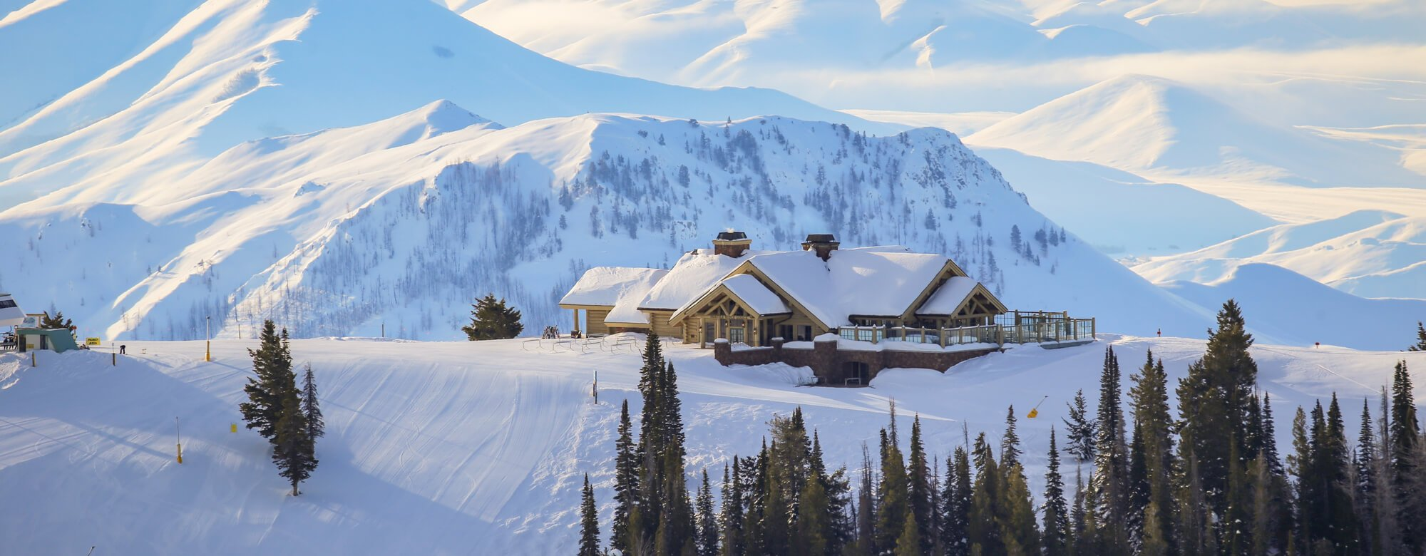 A home surrounded by snow on top of a mountain