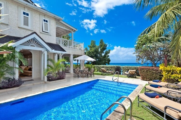 A beautiful Caribbean villa in Barbados with a  large pool in the the garden, and a view of the Caribbean Sea