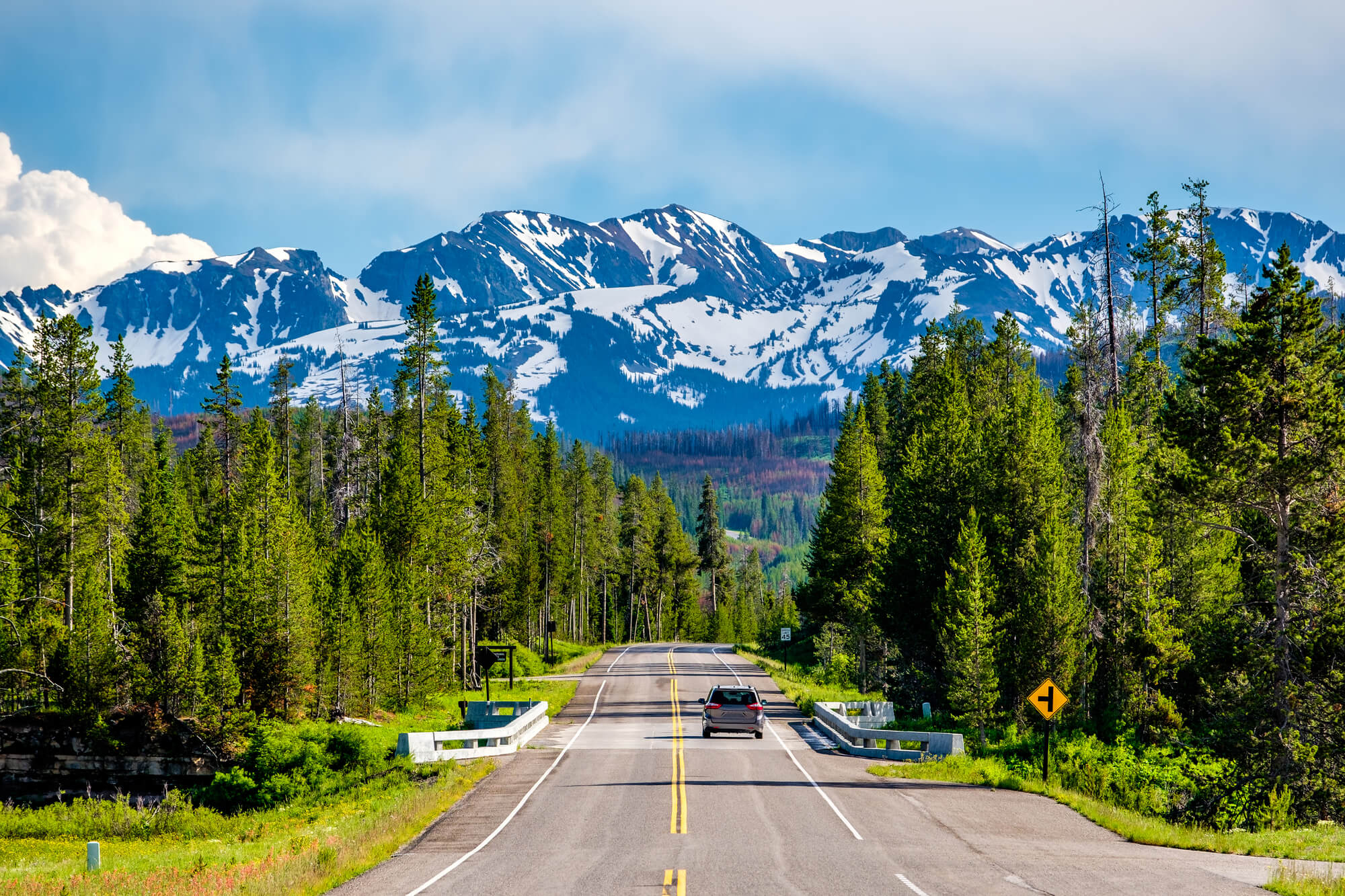 Road through Yellowstone with mountains in the distance