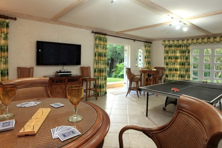 A room with a card table, ping pong and large television