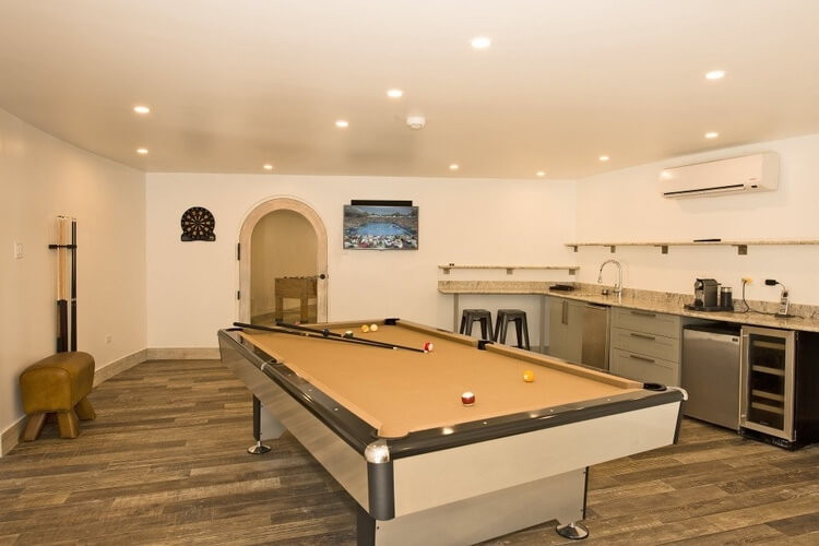 A room with a snooker table and small kitchen area
