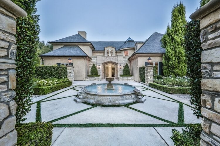 A stunning luxury villa in Beverly Hills with a water fountain  on the front patio