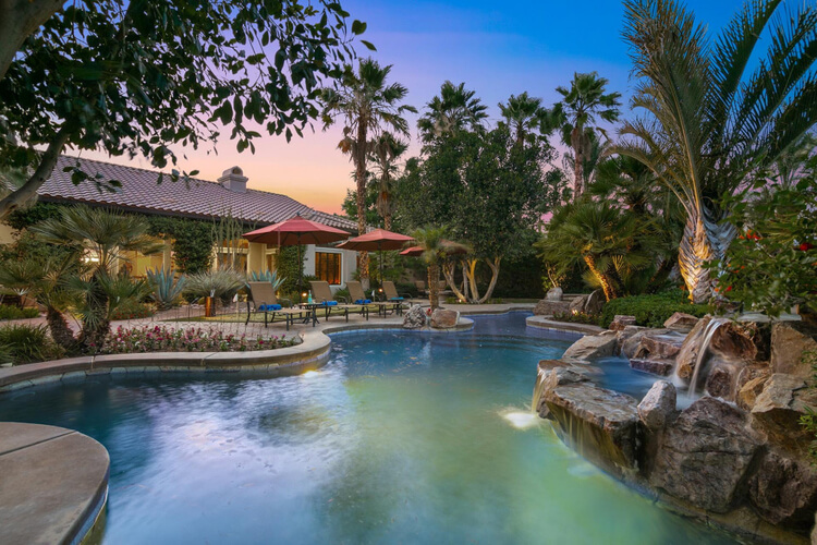 A luxury villa in La Quinta with a large resort-style pool, manicured tropical gardens and outdoor seating area